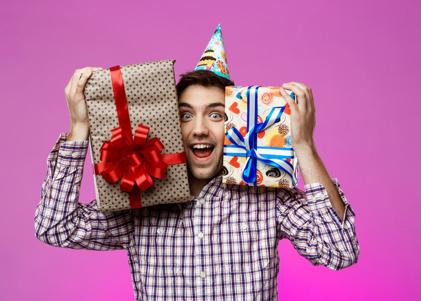 Happy man holding birthday gifts in boxes over purple background.
